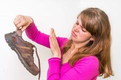 Smutsiga stinky skor för kvinnainnehav Royaltyfri Fotografi