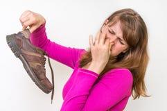 Smutsiga stinky skor för kvinnainnehav Arkivfoton