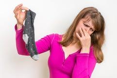 Smutsiga stinky sockor för kvinnainnehav Arkivbild