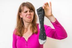 Smutsiga stinky sockor för kvinnainnehav Arkivfoton