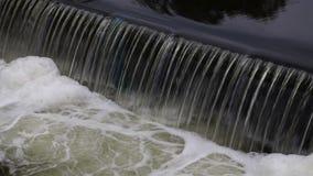 Smutsigt flodvatten som faller från klyfta och skum arkivfilmer
