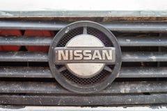 Smutsigt gammalt Nissan emblem p? ett elementgaller arkivbilder