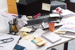 Smutsigt och belamrat skrivbord arkivbild