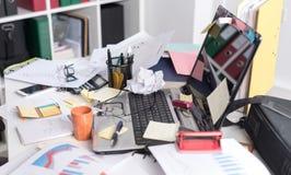 Smutsigt och belamrat skrivbord arkivbilder