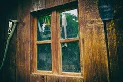 Smutsigt och dammigt fönster på en gammal träladugård, med funktionsdugliga hjälpmedel bak exponeringsglaset Stäng sig upp av gam fotografering för bildbyråer