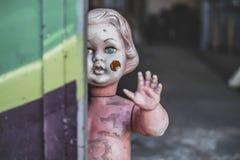 Smutsigt plast- naket behandla som ett barn - dockaanseendet vid dörren på metallen shoppar att se kusligt och jagat väva closeup arkivbild