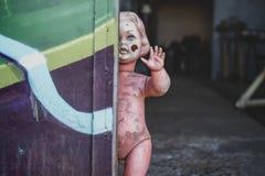 Smutsigt plast- naket behandla som ett barn - dockaanseendet vid dörren på metallen shoppar att se kusligt och jagat väva arkivbild