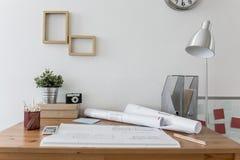 Smutsigt skrivbord med arkitekts plan Fotografering för Bildbyråer