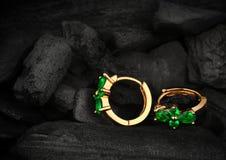 Smyckenörhängen med ädelstensmaragden på mörk kolbakgrund som är mjuk Arkivfoton