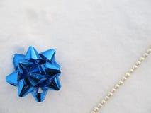 Smycken för garnering, pärlor och blått bugar på snö Arkivfoto