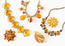 Smycken för kvinna` s Tappningsmyckenbakgrund Härliga ljusa bergkristallbroscher, braceletes, halsband och örhängen på vit Fl arkivfoton