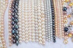 Smycken pryder med pärlor halsband som är färgrika på vit flanell royaltyfria bilder