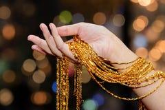 Smycken, tillbehör och f för halsband för kvinnahandhåll guld- arkivfoton