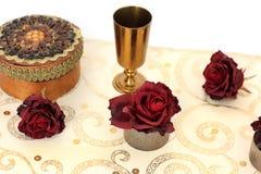 Smyckenask, rosor och en guld- bunke p? en vit bakgrund arkivbilder