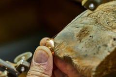 Smyckenproduktion Juvelerare genom att anv?nda s?gen f?r att skapa smycken arkivbilder