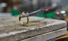 Smyckenproduktion Juveleraren g?r en guld- cirkel royaltyfri bild
