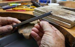 Smyckenproduktion Juveleraren g?r en guld- cirkel royaltyfria foton