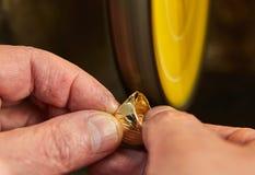 Smyckenproduktion Juveleraren polerar en guld- cirkel p? en slipmaskin royaltyfri foto