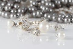 Smyckenuppsättningar för Closeup två av dubbade silver- och pärlaörhängen Arkivfoton