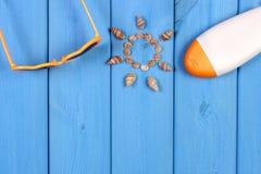 Snäckskal i form av solen, solglasögon och sollotion på blåttbräden, tillbehör för sommar, kopieringsutrymme för text Royaltyfria Foton