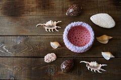 Snäckskal och koraller och korg på en träbakgrund med kopieringsutrymme för text royaltyfri foto