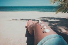 Snäckskal på det brunbrända flickabenet på den tropiska stranden i sommar Royaltyfria Bilder