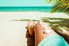 Snäckskal på det brunbrända flickabenet på den tropiska stranden i sommar Arkivbilder