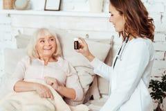 Snäll doktor som hemma tar omsorg av en gammal kvinna Arkivbilder