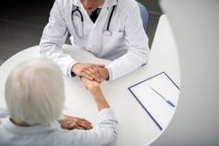 Snäll doktor som talar till patienten och rymmer hennes hand royaltyfria foton