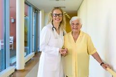 Snäll sjuksköterska Assisting Old Patient på hallet arkivbilder