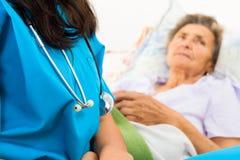 Snäll sjuksköterska med åldring Arkivbild