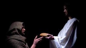 Snälla Jesus i krona av taggar som ger bröd för den hungriga hemlösa mannen, mirakel fotografering för bildbyråer