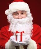 Snälla Santa Claus som ger xmas-gåva arkivbild