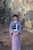 Snällt och angenämt av receptionist i kimonoklänning på lila- och vitfärg på den Himeji slotten arkivbild
