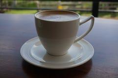 Snäsigt kaffe på den wood tabellen Royaltyfri Bild