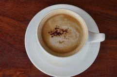 Snäsigt kaffe på den wood tabellen Arkivfoto