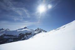 Snö-överträffade bergmaxima under solen Royaltyfria Bilder