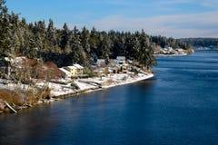 Snö-dammad av stad mellan trän och vattnet arkivfoton