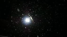 Snö faller långsamt i nattvinter lyktasken till och med snön långsam rörelse