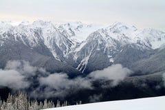 Snö-korkad bergskedja utöver ett snöig fält Arkivfoto
