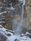 Snö, is och stenar som faller från en vertikal bergvägg Royaltyfria Foton