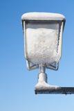 Snö och is täckte lampan framme av blå himmel i vintern Arkivfoto