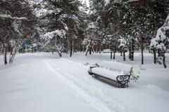 Snö på bänk parkerar in Arkivbild