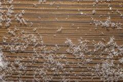 Snö på brunt gammalt bränt bräde royaltyfria bilder