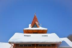 Snö på taket av trähuset Loftfönster av den triangulära shaen arkivbild