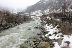 Snö, snöslask och stenar fodrar bankerna av den Sind floden Fotografering för Bildbyråer
