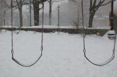 Snö som faller på tomma gungor i ett öde, parkerar Är är kallt och kusligt och ruffigt Royaltyfri Bild