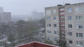 Snö som framme faller av det bosatta flerbostadshuset Bo lägenheter i vinter arkivfilmer