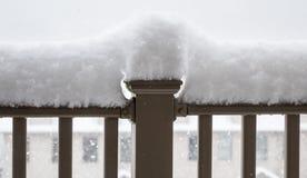 Snö som högt travas på räcket av balkongen Arkivbild