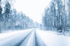 Snö-täckt öppen väg under en snöstorm i vinter väder för motsatt tillstånd arkivbild